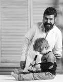 Ο παιδίατρος κρατά ότι το στηθοσκόπιο και ο βοηθός εξετάζουν το μικροσκόπιο Τύπος και παιδί με τον ευτυχή και πολυάσχολο γιατρό π Στοκ εικόνα με δικαίωμα ελεύθερης χρήσης