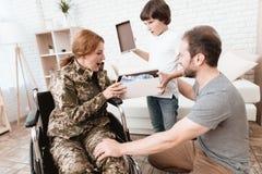 Ο παλαίμαχος γυναικών στην αναπηρική καρέκλα επέστρεψε από το στρατό Ο γιος και ο σύζυγος είναι ευτυχείς να την δουν Στοκ Φωτογραφία