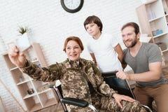 Ο παλαίμαχος γυναικών στην αναπηρική καρέκλα επέστρεψε από το στρατό Ο γιος και ο σύζυγος είναι ευτυχείς να την δουν Στοκ φωτογραφίες με δικαίωμα ελεύθερης χρήσης
