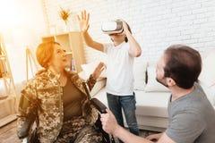 Ο παλαίμαχος γυναικών στην αναπηρική καρέκλα επέστρεψε από το στρατό Το αγόρι εξετάζει τα γυαλιά εικονικής πραγματικότητας Στοκ Φωτογραφίες