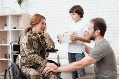 Ο παλαίμαχος γυναικών στην αναπηρική καρέκλα επέστρεψε από το στρατό Ο γιος και ο σύζυγος είναι ευτυχείς να την δουν Στοκ φωτογραφία με δικαίωμα ελεύθερης χρήσης
