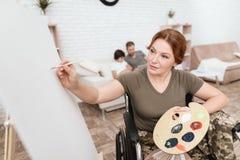 Ο παλαίμαχος γυναικών στην αναπηρική καρέκλα επέστρεψε από το στρατό Μια γυναίκα σε μια αναπηρική καρέκλα επισύρει την προσοχή στ Στοκ εικόνα με δικαίωμα ελεύθερης χρήσης
