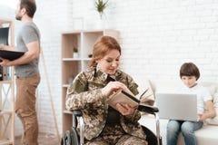Ο παλαίμαχος γυναικών στην αναπηρική καρέκλα επέστρεψε από το στρατό Μια γυναίκα σε μια αναπηρική καρέκλα που διαβάζει ένα βιβλίο Στοκ Εικόνες