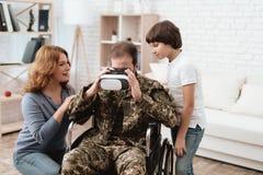 Ο παλαίμαχος σε μια αναπηρική καρέκλα επέστρεψε από το στρατό Ένα άτομο σε ομοιόμορφο σε μια αναπηρική καρέκλα με την οικογένειά  Στοκ Φωτογραφία