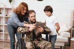 Ο παλαίμαχος σε μια αναπηρική καρέκλα επέστρεψε από το στρατό Ένα άτομο σε ομοιόμορφο σε μια αναπηρική καρέκλα με την οικογένειά  Στοκ φωτογραφία με δικαίωμα ελεύθερης χρήσης