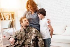 Ο παλαίμαχος σε μια αναπηρική καρέκλα επέστρεψε από το στρατό Ένα άτομο σε ομοιόμορφο σε μια αναπηρική καρέκλα με την οικογένειά  Στοκ εικόνες με δικαίωμα ελεύθερης χρήσης