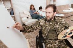 Ο παλαίμαχος στην αναπηρική καρέκλα επέστρεψε από το στρατό Το άτομο σε μια αναπηρική καρέκλα σύρει Χρώμα και βούρτσα λαβής ατόμω Στοκ Εικόνες