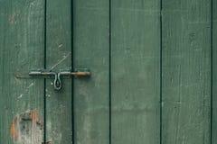 Ο παλαιοί και σκουριασμένοι σύρτης και η κλειδαριά πορτών στην πράσινη ξύλινη πόρτα Σκοτεινός τόνος στοκ φωτογραφία με δικαίωμα ελεύθερης χρήσης