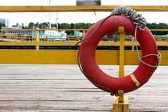 Ο παλαιός κόκκινος κύκλος της ζωής κρεμά στον τρόπο στη σκάλα που οδηγεί στο σκάφος Στοκ Φωτογραφίες