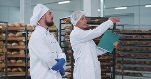 Ο παλαιός μηχανικός ατόμων βιομηχανίας αρτοποιείων και ο νέος αρτοποιός με ένα πηγούνι διοργανώνουν μια συνεδρίαση στο τμήμα αρτο απόθεμα βίντεο