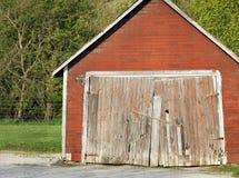 Ο παλαιός τρύγος έριξε/σιταποθήκη με τη μέγιστη στέγη, την πλαστή επικεράμωση τούβλου και την παλαιά ξύλινη πόρτα στοκ φωτογραφία με δικαίωμα ελεύθερης χρήσης