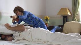 Ο παλαιότερος ύπνος αδελφών στο κρεβάτι και ο μικρότερος αδερφός τον ξυπνούν παίζοντας το βιολί Ο τύπος ρίχνει το μαξιλάρι στο br απόθεμα βίντεο