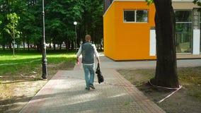 Ο πανέμορφος νεαρός άνδρας στα ενδύματα τζιν με την τσάντα στο χέρι του περπατά κάτω από την οδό απόθεμα βίντεο