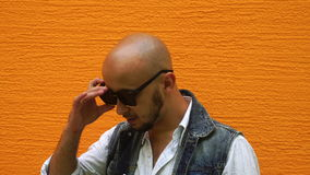 Ο πανέμορφος νεαρός άνδρας στα ενδύματα τζιν με φορά τα μαύρα γυαλιά ηλίου φιλμ μικρού μήκους