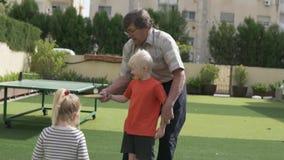 Ο παππούς διδάσκει τον εγγονό για να παίξει την επιτραπέζια αντισφαίρ φιλμ μικρού μήκους