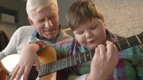 Ο παππούς διδάσκει τον εγγονό του πώς να παίξει την κιθάρα Ένα ηλικιωμένο άτομο διδάσκει ένα νέο παχύ παιδί για να παίξει την κιθ απόθεμα βίντεο