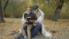 Ο παππούς και ο εγγονός διαβάζουν το βιβλίο στο πάρκο φθινοπώρου απόθεμα βίντεο