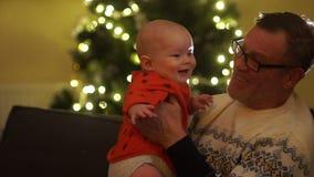 Ο παππούς και ο εγγονός κάθονται κοντά στο χριστουγεννιάτικο δέντρο Το παιδί εξετάζει το πλαίσιο στην έκπληξη γιορτάστε την οικογ απόθεμα βίντεο