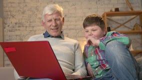 Ο παππούς και ο εγγονός κάθονται στον ενδιαφέροντα κινηματογράφο των καναπέδων και προσοχής στο lap-top, γέλιο Εγχώρια άνεση απόθεμα βίντεο