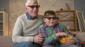 Ο παππούς και ο εγγονός κάθονται στον καναπέ και προσέχοντας έναν τρισδιάστατο κινηματογράφο στα τρισδιάστατα γυαλιά, που τρώνε τ φιλμ μικρού μήκους