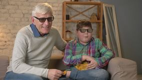 Ο παππούς και ο εγγονός κάθονται στον καναπέ και προσέχοντας έναν τρισδιάστατο κινηματογράφο στα τρισδιάστατα γυαλιά, τρώγοντας τ φιλμ μικρού μήκους