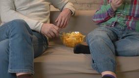 Ο παππούς και ο εγγονός κάθονται στον καναπέ και τη TV προσοχής, τρώγοντας τα τσιπ Εγχώρια άνεση, οικογένεια idyll, cosiness απόθεμα βίντεο