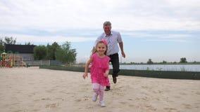 Ο παππούς προφθάνει την εγγονή της Τα οικογενειακά παιχνίδια στην παραλία Τρέχουν στη κάμερα r φιλμ μικρού μήκους