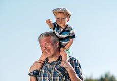 Ο παππούς φέρνει το αγόρι μικρών παιδιών εγγονών στους ώμους του στοκ εικόνες