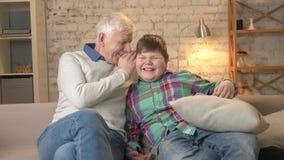 Ο παππούς ψιθυρίζει στο αυτί του εγγονού του ένα αστείο μυστικό, κουτσομπολιό Νέο παχύ γέλιο αγοριών Εγχώρια άνεση, οικογένεια απόθεμα βίντεο