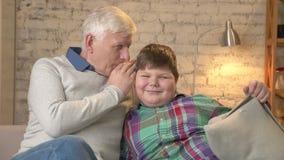 Ο παππούς ψιθυρίζει στο αυτί του εγγονού του ένα αστείο μυστικό, κουτσομπολιό Νέο παχύ αγόρι που γελά, χαμόγελο Εγχώρια άνεση απόθεμα βίντεο