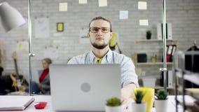 Ο παραγωγικός σοβαρός συγκεντρωμένος επιχειρηματίας που κλίνει την πίσω εργασία γραφείων λήξης για το lap-top, αποτελεσματικός δι απόθεμα βίντεο