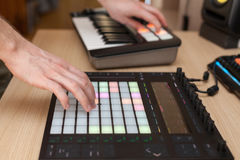 Ο παραγωγός κάνει μια μουσική στον επαγγελματικό ελεγκτή παραγωγής με τα μαξιλάρια κουμπιών ώθησης στοκ εικόνες