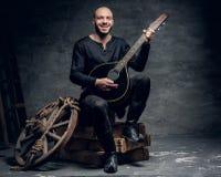 Ο παραδοσιακός λαϊκός μουσικός που ντύνεται στα εκλεκτής ποιότητας κελτικά ενδύματα κάθεται σε ένα ξύλινο κιβώτιο και παίζει το μ Στοκ εικόνες με δικαίωμα ελεύθερης χρήσης