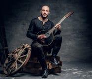 Ο παραδοσιακός λαϊκός μουσικός που ντύνεται στα εκλεκτής ποιότητας κελτικά ενδύματα κάθεται σε ένα ξύλινο κιβώτιο και παίζει το μ Στοκ Εικόνα