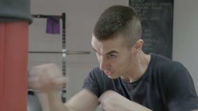 Ο παρακινημένος νέος αρσενικός μπόξερ πρωτοπόρων που χτυπά γρήγορα τη punching τσάντα χωρίς φθορά φορά γάντια - φιλμ μικρού μήκους
