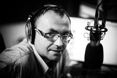 Ο παρουσιαστής ή ο οικοδεσπότης στη φιλοξενία ραδιοσταθμών παρουσιάζει για το ραδιόφωνο ζωντανό στο στούντιο Στοκ Φωτογραφίες