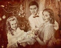Ο πατέρας αγκαλιάζει τη σύζυγό του με την κόρη και το χριστουγεννιάτικο δέντρο επιδέσμου Στοκ εικόνα με δικαίωμα ελεύθερης χρήσης