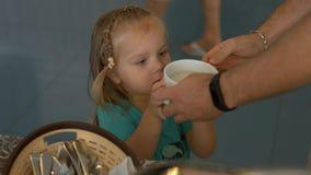 Ο πατέρας βάζει το κουάκερ στη μικρή κόρη του για το πρόγευμα Στοκ Εικόνες