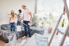 Ο πατέρας βοηθά τα παιδιά με τη ζωγραφική ενός τοίχου στοκ εικόνα