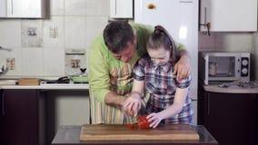 Ο πατέρας βοηθά την κόρη με το κάτω σύνδρομο για να κόψει το πιπέρι κουδουνιών απόθεμα βίντεο