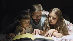 Ο πατέρας διαβάζει ένα παραμύθι για τα παιδιά ολονυκτίς απόθεμα βίντεο