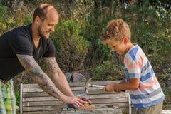 Ο πατέρας διδάσκει το γιο πώς να χρησιμοποιήσει ένα σφυρί στοκ εικόνες