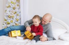 Ο πατέρας και λίγος γιος βρίσκονται στο κρεβάτι Ανοίγουν τα δώρα Χριστουγέννων Στοκ εικόνες με δικαίωμα ελεύθερης χρήσης