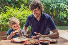 Ο πατέρας και ο γιος δοκιμάζουν τα ινδικά τρόφιμα σε έναν καφέ στην οδό στοκ εικόνες
