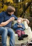 Ο πατέρας και ο γιος κάθονται σε έναν ξύλινο πάγκο στο πάρκο και το Δρ Στοκ εικόνες με δικαίωμα ελεύθερης χρήσης
