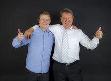 Ο πατέρας και ο γιος με τους αντίχειρες υπογράφουν επάνω Στοκ Εικόνες