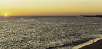 Ο πατέρας και ο γιος προσέχουν το ηλιοβασίλεμα στην άκρη της θάλασσας, στην παραλία στοκ εικόνα