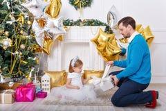 Ο πατέρας και η κόρη ανοίγουν τα δώρα στο χριστουγεννιάτικο δέντρο Στοκ Φωτογραφίες