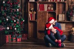 Ο πατέρας και η κόρη κάθονται στο πάτωμα που αγκαλιάζει και που περιμένει τα Χριστούγεννα στοκ φωτογραφίες