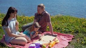Ο πατέρας και η κόρη μητέρων τρώνε την πίτσα από τη θάλασσα ακτών απόθεμα βίντεο